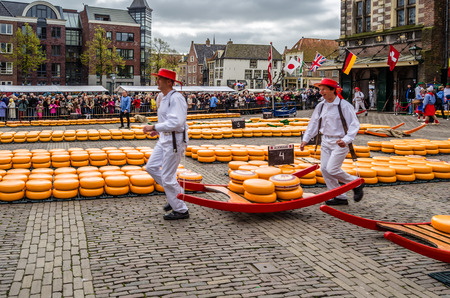 ALKMAAR, THE NETHERLANDS - APRIL 22, 2016: Typical cheese market at the Waagplein in the city of Alkmaar (the Netherlands), one of the only four traditional Dutch cheese markets still in existence and one of the countrys most popular tourist attractions.