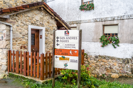 SOTO DE AGUES, SPAIN - NOVEMBER 5, 2017: Sign indicating mountain routes and touristic information in the village of Soto de Agues in Asturias, northern Spain Editorial