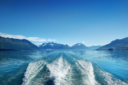Waves from the boat and deep blue sky under the mountain of Alaska photo