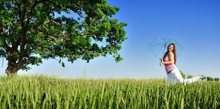 Young woman in a field with umbrella panoramic Stock Photo
