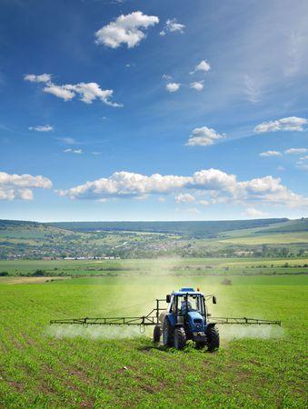 ploegen: Landbouw trekker plowing en spuiten op veld Stockfoto