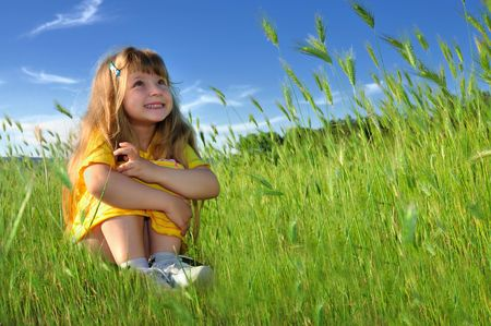 Dreaming girl in a fresh green grass Stock Photo