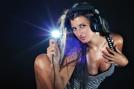 Hot beautiful girl like a dj and black background