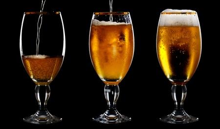 Beer into glass on a black background Reklamní fotografie
