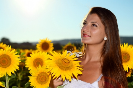 Beautiful girl in a field, holding small sunflower photo