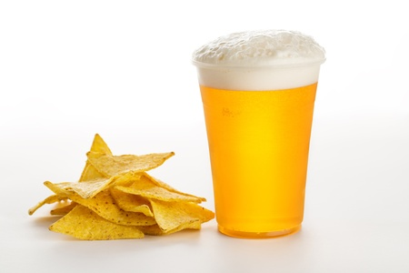 Glass of beer and Mexican tortilla chips isolated on white background photo