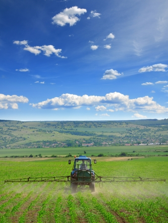 Farming tractor plowing and spraying on field vertical photo