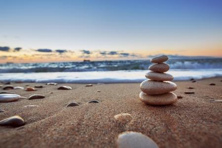 Pietre equilibrio sulla spiaggia, tiro sunrise Archivio Fotografico