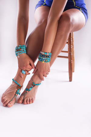 foot model: Woman posing with summer styles bracelets and rings, studio shot