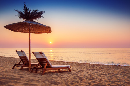 dramatic sunrise: Vivid sunrise on a beautiful sandy beach with sunshade  Stock Photo