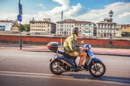 Muchacho de la vespa de conducción en las calles de Florencia, Italia