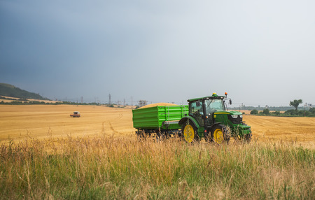 Varna, Bulgaria - June 20, 2015: Unidentified farmer driving a John Deere 6150 R agricultural tractor and trailer full of grain. John Deere 6150 R was manufactured in 2003-2008 in Germany.