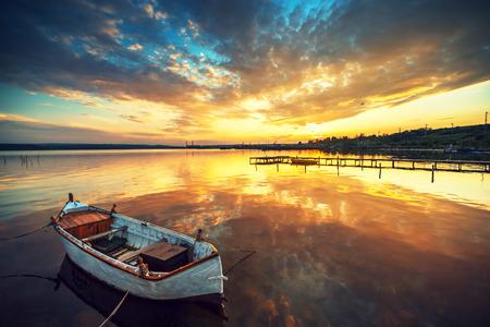 reflexion: Barco en el lago con una reflexión en el agua al atardecer Foto de archivo
