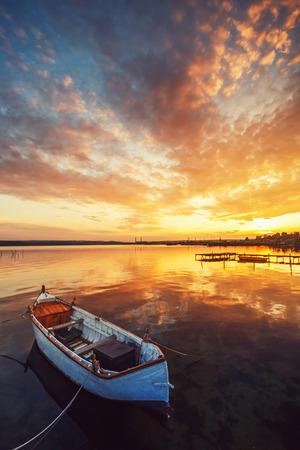 석양에 물에 반사와 호수에 보트
