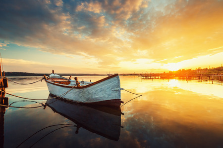 fishing boats: Boat on lake with a reflection in the water at sunset
