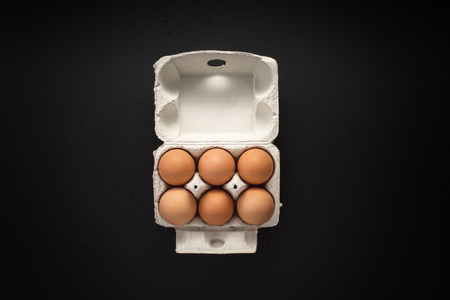 chicken and egg: Chicken eggs in box isolated on a black surface