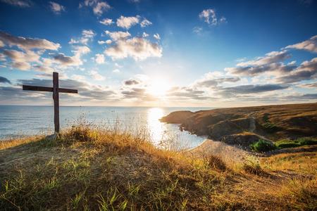 멋진 일출과 야생 해변에서 기독교 십자가