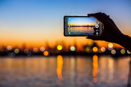Wonderful sunset over sea harbor, tourist taking a picture of the seaport 写真素材