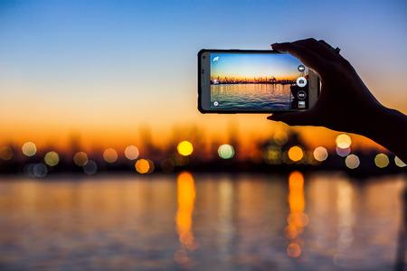 Prachtige zonsondergang over zee haven, toeristische nemen een foto van de zeehaven