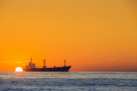 Fisherman sailling with his boat on beautiful sunrise over the sea