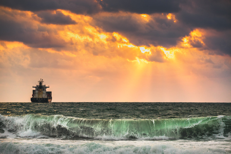 ocean water: Sun setting at the sea with sailing cargo ship, scenic view Stock Photo