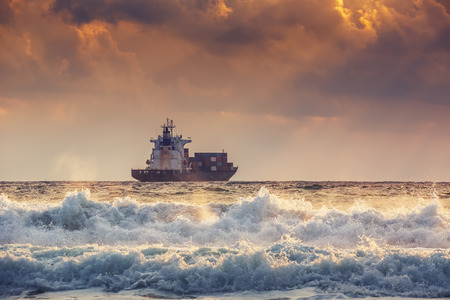 pier: Sun setting at the sea with sailing cargo ship, scenic view Stock Photo