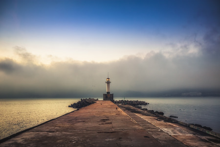 moody sky: Beautiful seascape with lighthouse and moody sky at the sunset
