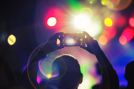 concert background: Silhouette of a fan using smartphone to take a video at a concert