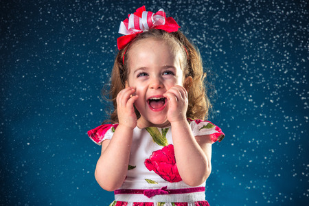 cute girl: winter, holidays, christmas concept - beautiful little girl having fun with snow flakes