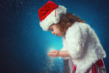 young: winter, holidays, christmas concept - beautiful little girl having fun with snow flakes, studio shot