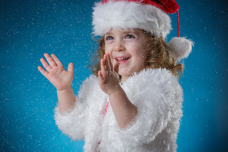 cute girl smiling: winter, holidays, christmas concept - beautiful little girl having fun with snow flakes, studio shot
