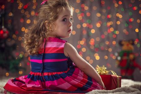 winter girl: Winter, holidays, christmas concept - beautiful little girl waiting Santa Claus, bokeh bakcground