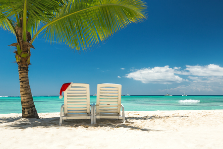 Panorama of sun loungers with Santa hat at beautiful tropical beach with white sand and turquoise water, perfect Christmas vacation