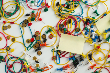 drawing pins: Colourful paper clips, elastic rubber bands, drawing pins thumb tacks and sticky notes as a texture background.