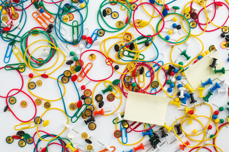 drawing pins: Colourful paper clips, elastic rubber bands, drawing pins thumb tacks as a texture background. Office concept.