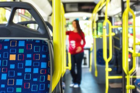 Silueta de una mujer embarazada que viaja con autobus público o de tranvía, durante su viaje al trabajo / escuela