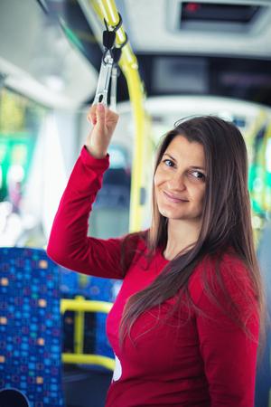 Portret van een lachende jonge zwangere vrouw reizen met het openbaar vervoer Stockfoto