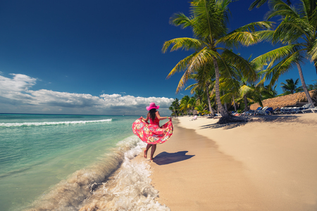 Carefree young woman  walking on the tropical sandy beach, Saona island, Dominican Republic Stok Fotoğraf