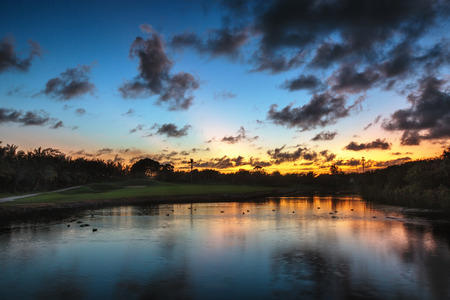 birds lake: Beautiful sunset over the lake near the golf course in a tropical resort in Punta Cana, Dominican Republic