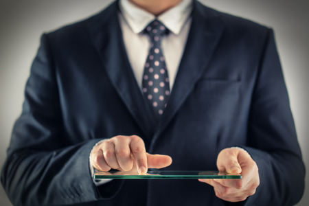Business and technology concept. Man in suit holding and showing transparent mobile device at office, close up 写真素材