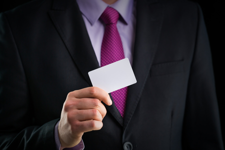 message card: Businessman in elegant suit and with a tie, shows business card with copy space, studio shot Stock Photo