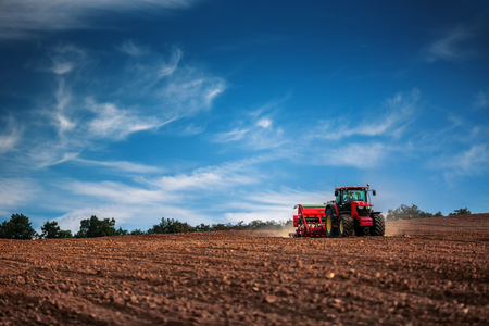 plowed field: Farmer in tractor preparing farmland with seedbed for the next year