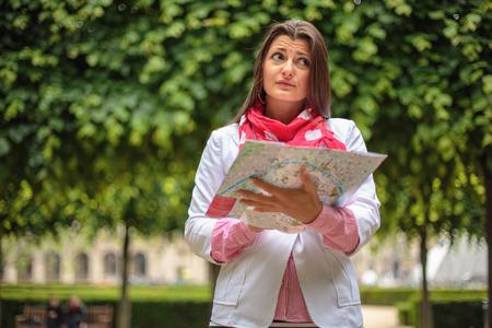 persona confundida: Confundido joven de la ciudad la celebraci�n de Mapas en jard�n de las Tuller�as en Par�s, Francia