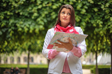 confused: Confused young girl holding city Maps in Tuileries garden Paris, France
