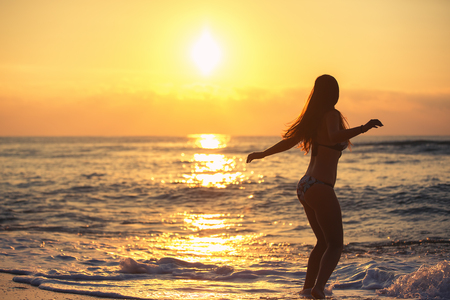 summer holiday bikini: Silhouette of carefree woman on the beach at sunrise