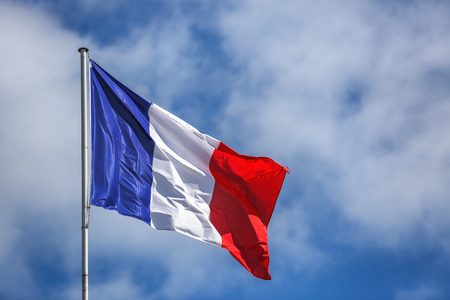 on the sky background: Flag of France, waving in the wind, on the sky