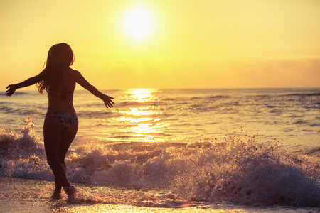 girl on a beautiful background: Silhouette of carefree woman on the beach at sunrise