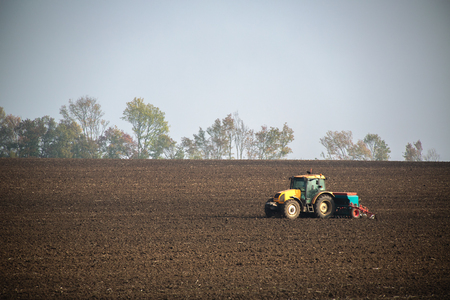 seeding: Farmer with tractor seeding crops at field
