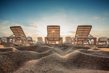 getaways: Beach chairs on the sands at sunrise, summer vacation getaways concept