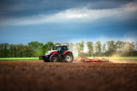 plough machine: Farmer in tractor preparing land with seedbed cultivator